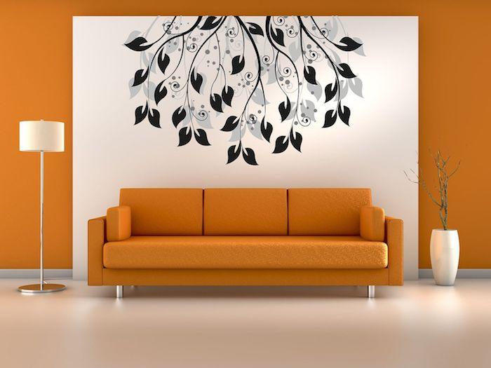 eine große orange wand und ein weißes bild mit vielen schwarzen ästen und blättern, ein oranges sofa und eine weiße lampe