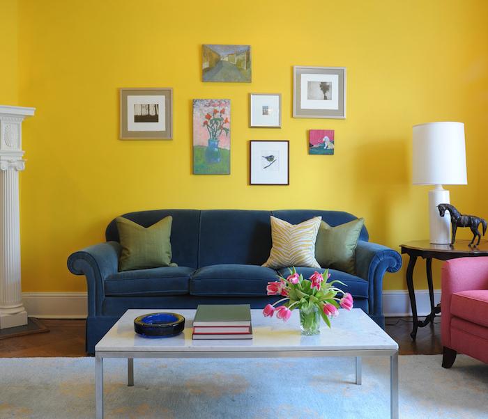 große gelbe wand mit vielen bildern und ein kleines blaues sofa mit grünen und gelben kisseen, ein kleiner weißer tisch mit einer vase mit violetten blummen und grünen blättern, ein kleines schwarzes pferd und eine weiße lampe