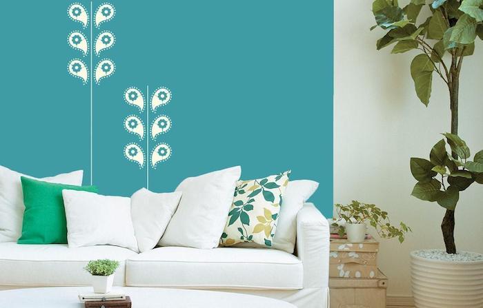große blaue wand mit weißen blumen, ein wohnzimmer mit einem weißen sofa mit weießn und grünen kissen mit blumen, ein topf mit einer großen grünen pflanze