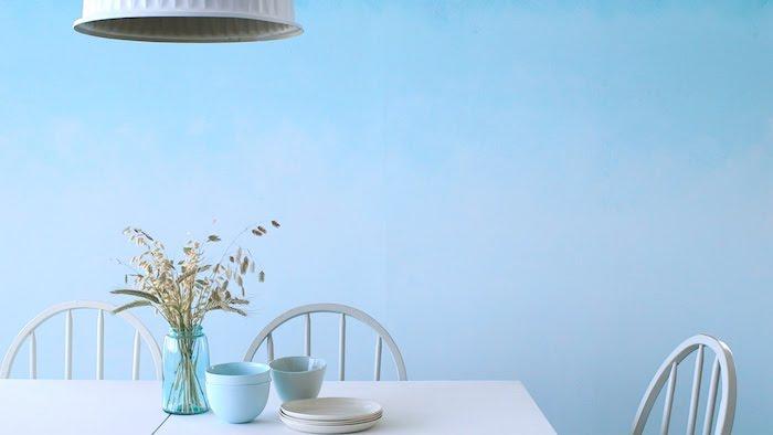 eine große blaue wand und ein weißer tisch mit einer blauen vase mit pflanzen, kleine weiße teller und zwei blaue tassen und drei weiße stühle