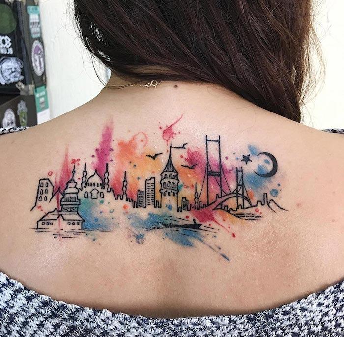 eine junge frau mit einem bunten aquarell tattoo mit einer stadt und mit einem schwarzen halbmont, schwarzen sternnen und vielen schwarzen fliegenden vögeln