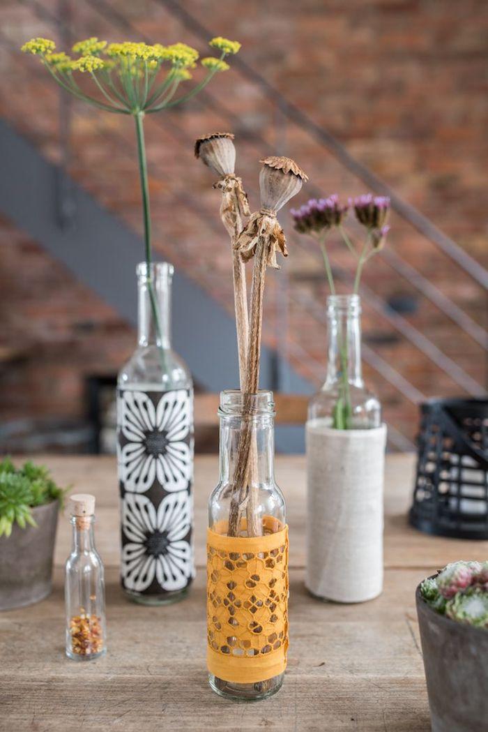 frühlingsdekoration basteln mikt alten flaschen aus glas und mit kleinen braunen, violetten und gelben blumen, alte flaschen recyceln ideen