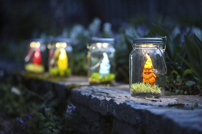gartendekoration ideen mit alten gläsern und mit kleinen zwergen mit gelben und blauen hüten, alten gläser recyceln ideen