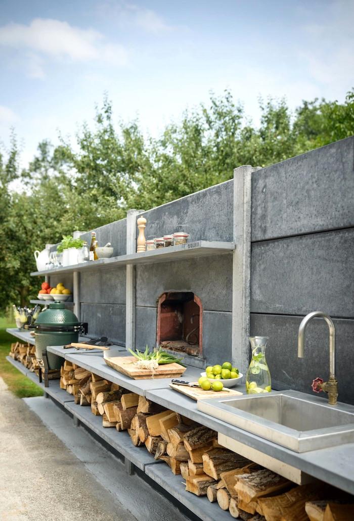 blauer himmel mit weißen wolken und eine graue küche mit einem waschbecken und ein kamin und viele scheite, ein garten mit grünen bäumen