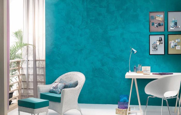 eine große blaue wand und zwei weiße stühle miz blauen kissen, ein kleiner weißer schreibtisch mit einer kleinen grauen lampe, wandfarbe blau