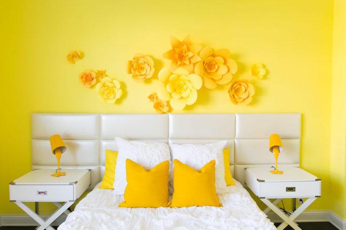 wand streichen ideen muster, ein bett mit kleinen gelben und weißen kissen und zwei kleine gelbe lampen, eine gelbe wand mit großen gelben blumen