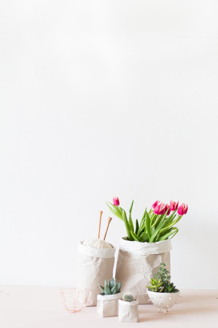 weiße wand, ein kleiner weißer blumentopf aus einer weißen papiertüte und mit einem kleinen grünen kaktus, papiertüten selber basteln, ein blumentopf mit grünen blättern und mit violetten tulpen