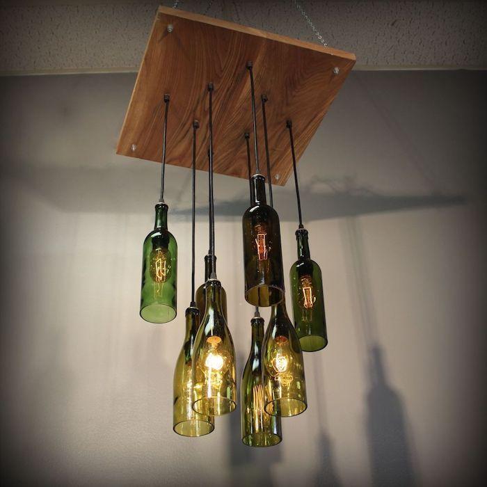 große hängelampe mit vielen geschnittenen grünen und schwarzen weinflschen aus glas und mit ggelben glühbirnen