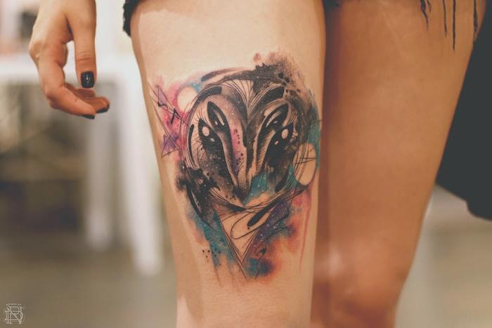 hand einer frau mit einem schwarzen nagellack, ein bein mit einem großen bunten watercolor tattoo mit einer schwarzen eule mit schwarzen augen und mit mond und sonne, tattoo aquarell ideen