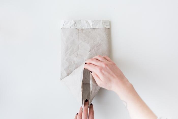 hand mit einer kleinen schwarzen tätowierung am handgelenk und einem schwarzen nagellack und eije gfefaltete alte weiße papiertüte