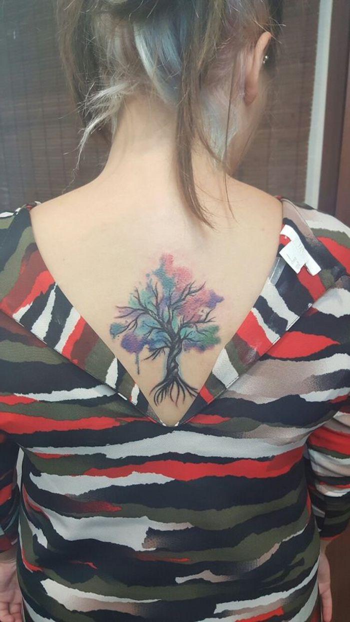 eine junge frau mit einem rücken mit einem kleinen tattoo watercolor mit einem schwarzen kleinen baum mit blauen und violetten blättern, blaue haare