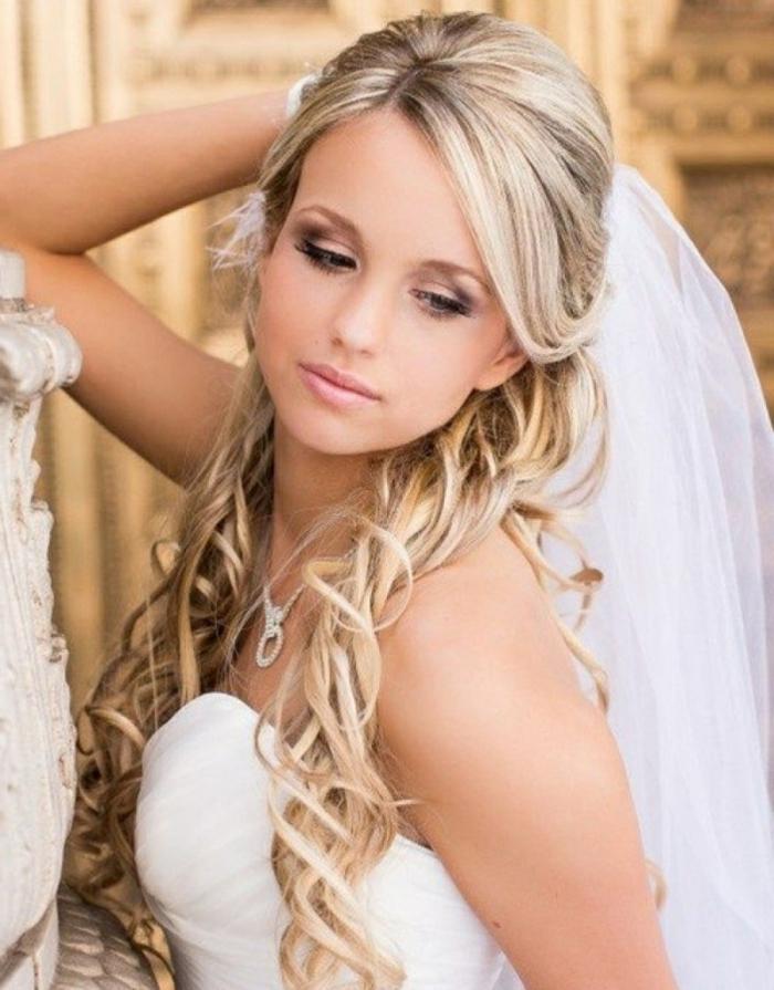 eine junge Braut mit langem Schleier, eine weiße Kette, lange blonde Haare mit lässigen Locken, Frisuren testen