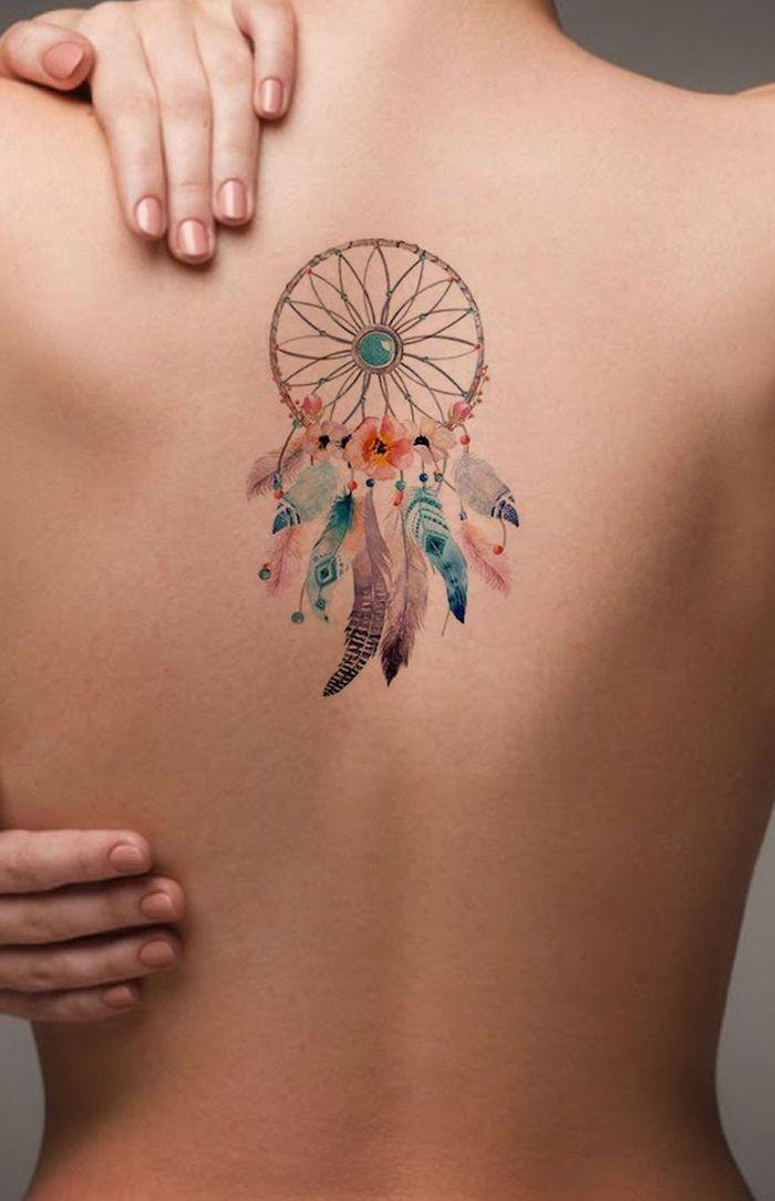 ein traumfänger tattoo aquarell mit vielen kleinen und großen pinken, violetten und blauen federn und mit orangen und violetten blumen, eine frau mit einem rücken tattoo watercolor