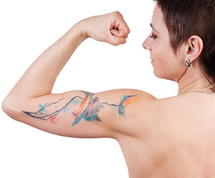 eine starke junge frau mit einer hand mit einem arm tattoo watercolor mit einem fliegenden blauen vogel und blauen bergen