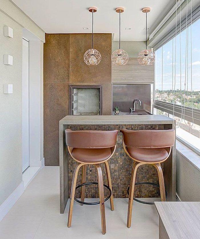 eine terrasse mit einer außenküche mit einem waschbecken, zwei braunen stühlen und drei lampen, eine außenküche selber bauen ideen