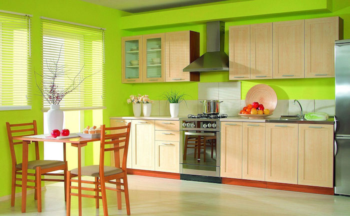 ein tisch aus holz und zwei braune stühle aus holz, eine küche mit grünen wänden und mit braunen möbeln, wand streichen muster