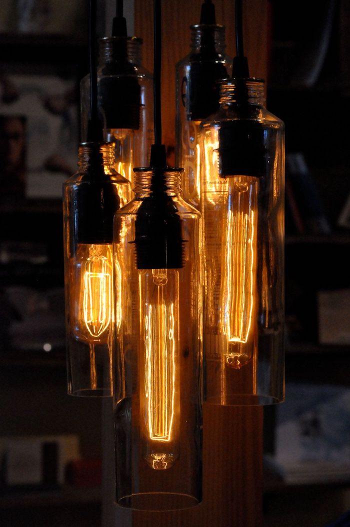 große lampe aus vielen geschnittenen alten flaschen für wein und aus glas und mit großen orangen glühbirnen