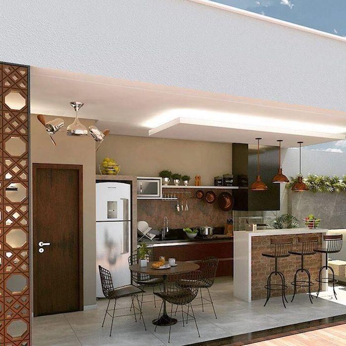 ein kleiner brauner tisch und stühle, drei braune lampen in einer außenküche mit einem waschbecken und einem elektroherd und eine braune tür aus holz