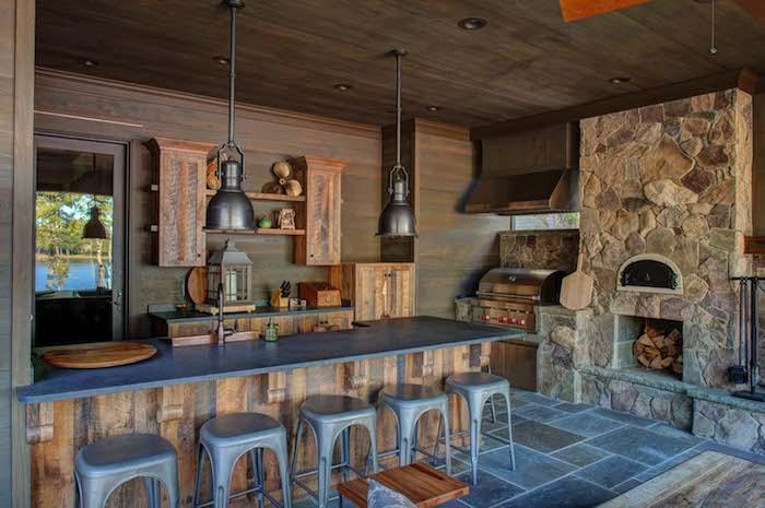 fünf graue stühle und ein grauer tisch, eine outdoor küche mit grauen lampen und einem kamin aus steinen und einem waschbecken