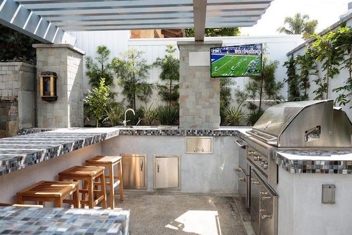 braune stühle aus holz und eine küche mit einem waschbecken und einem backofen und einem elektroherd und tv, eine außenküche bauen ideen