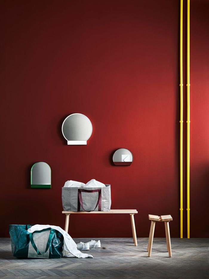 rote Wände, drei kleine Spiegel, kleiner Tisch und kleiner Stuhl, grauer Boden