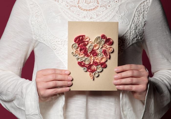 junge frau mit einem weißen kleid und eune rote wand und eine kleine karte mit einem roten quiling herzen
