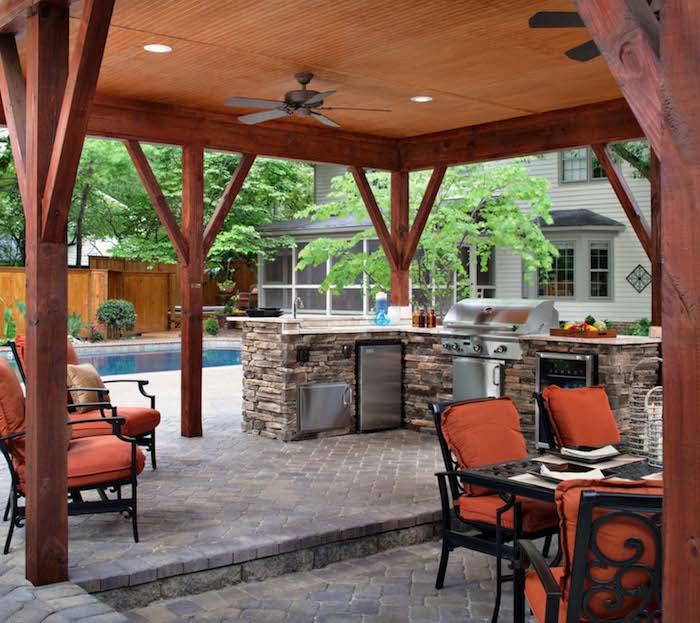 küche mit einem herd und einem grill und einem waschbecken, ein grauer boden und stühle mit orangen kissen