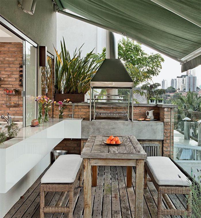 ein tisch aus holz und zwei bänke, zwei vasen mit blumen, ein garten mit einer mini küche und einem waschbecken und einem herd