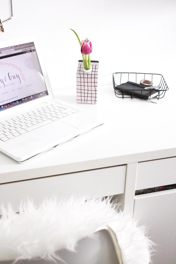 ein laptop und ein weißer schreibtisch und eine kleine weiße vase aus einem alten tetra pack und mit einer violetten tulpe mit grünen blättern