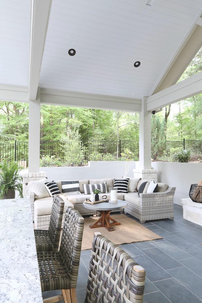 graue stühle aus rattan und ein weißer tisch, ein weißes haus und ein garten mit grünen pflanzen, graue sofas mit weißen und blauen kissen, ein kleiner tisch und eine kerze