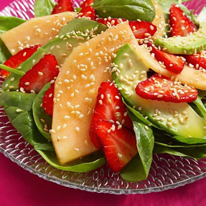 Gartensalat, Erdbeeren, Zuckermelone, Avocado Salat mit Sesam, in einer gläsernen Schale