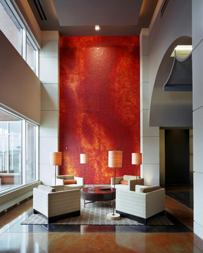 rote Wand, runder Tisch, vier Sessel, vier Lampen, ein bunter Teppich, schöne Farbkombinationen