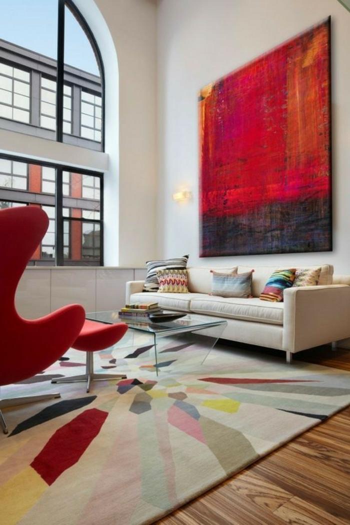Bild in roter und schwarzer Farbe, bunter Teppich, beiges Sofa, Tisch aus Glas, roter Sessel, schöne Farbkobinationen
