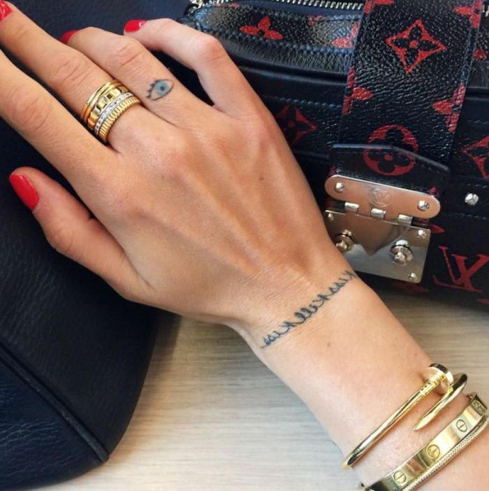Tattoos am Ringfinger und Handgelenk, goldene Ringe und Armbänder, roter Nagellack