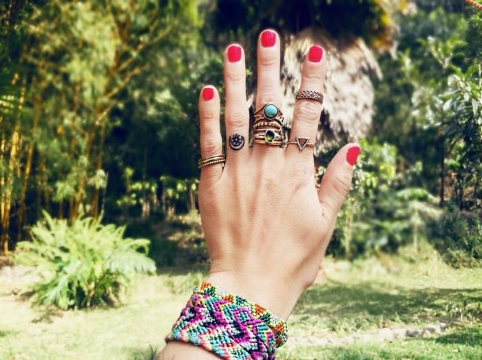 Bunte Armbänder und viele Ringe mit Steinen, kleines Tattoo am Ringfinger, roter Nagellack