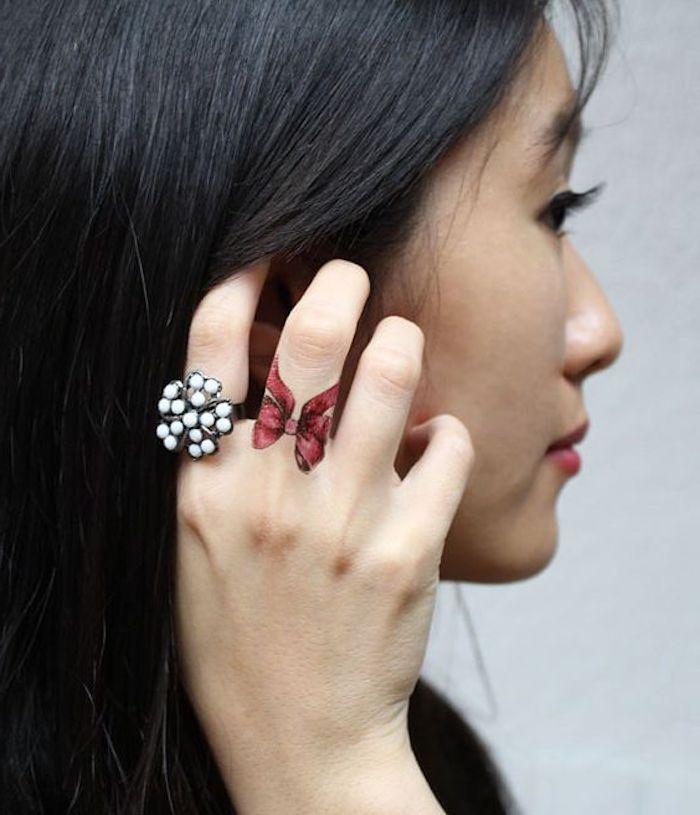 Farbiges Tattoo am Mittelfinger, rote Schleife, Ring mit weißen Steinen, schwarze glatte Haare