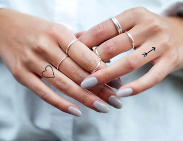 Zwei kleine Finger Tattoos, Herz und Pfeil, silberne Ringe, weißer Nagellack