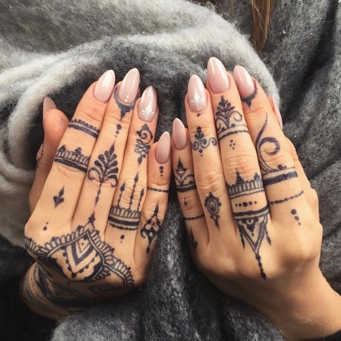 Henna Tattoos an bedien Händen, Nude-Nagellack, spitze Nägel, grauer Pullover