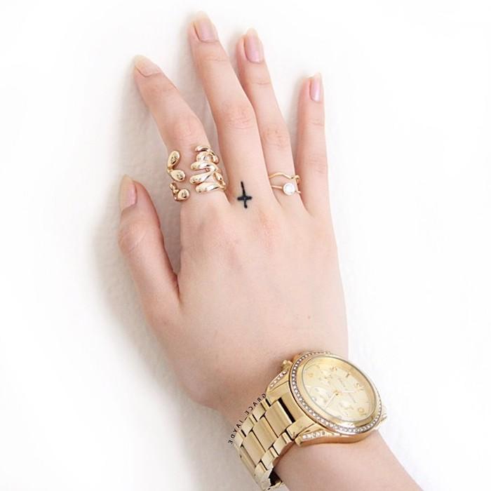 Kleines Tattoo am Mittelfinger, schwarzes Kreuz Tattoo, goldene Ringe und Armbanduhr