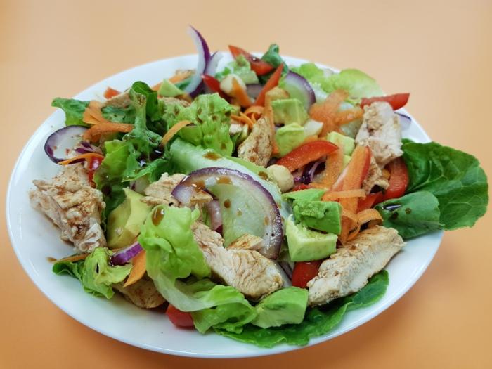 Grüne Salatblätter, roter Zwiebel, geriebene Möhren, Avocado im Salat