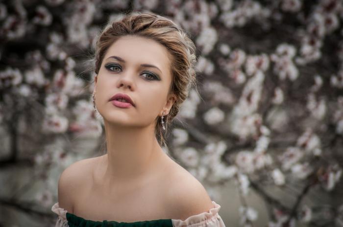 frisuren für dünnes haar gebundene haare einer jungen dame, dezenter schmuck, ohrringe, schöne schminke mit rosaroten lippen und grünen schatten, schulterloses kleid