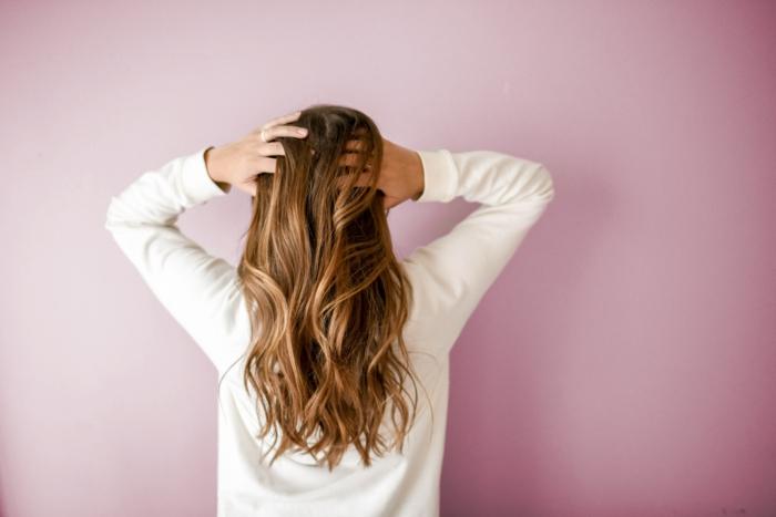 haar frisuren wild und locker, beachwaves, blonde haare, dunkelblond, weißer oberteil, rosa hintergrund