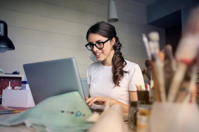 haar frisuren ideen alltäglich ins büro gehen und stilvoll sein, eine junge frau sitzt am computer und arbeitet, gebundene haare, lockig gemacht