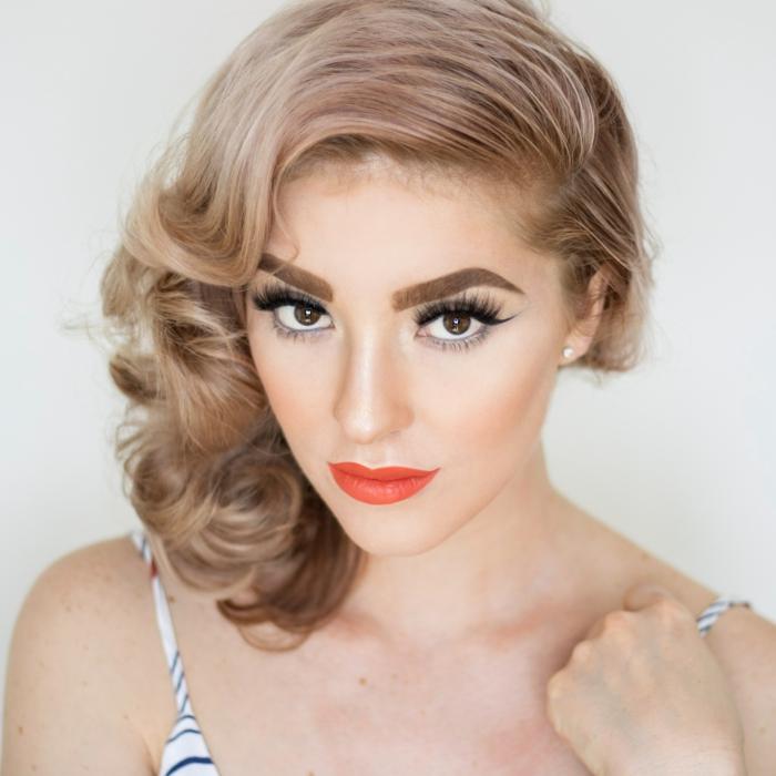 volumenwelle frisur ideen, blonde haare mit rosaroten strähnen, rote lippen, dicke braune augenbrauen, große augen