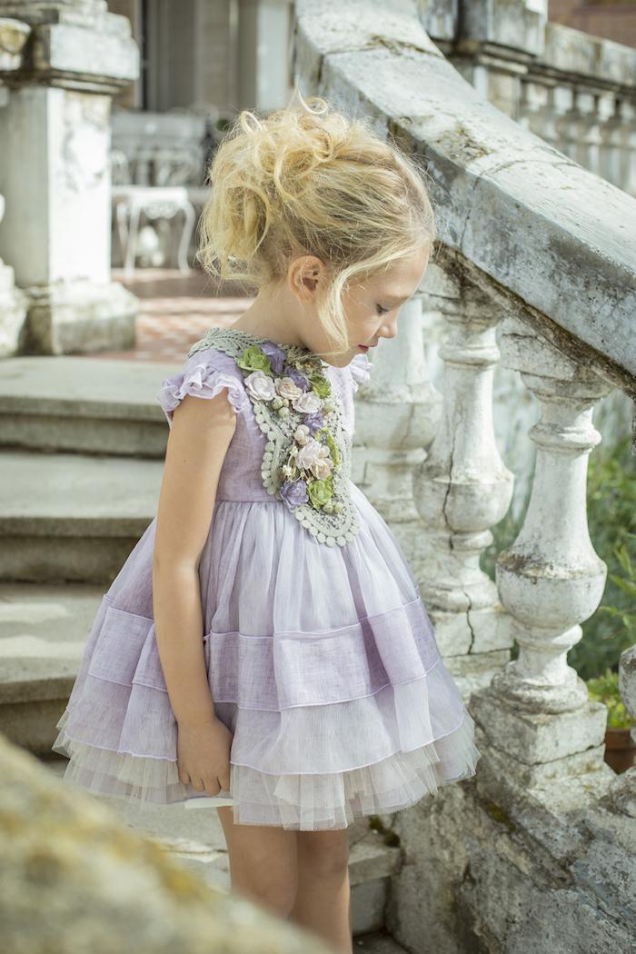 Kinderfrisuren für besondere Anlässe, Messy Dutt, lange blonde Haare, lilafarbenes Kleid mit Tüll und Blumen Applikationen
