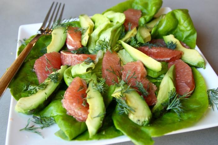 Grapefruit, Avocado im Salat, Dill als Dekoration in einem weißen Teller mit goldenen Gabel