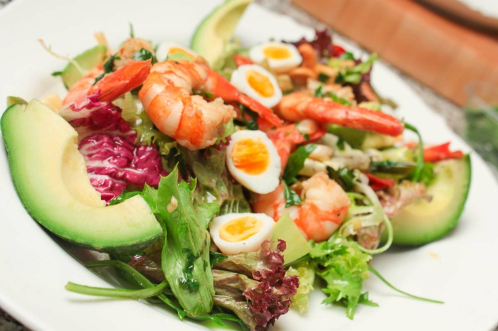 raffinierte Salate, kleine Eier, roter Kohl, Garnellen, ein Salat mit vielen gemischten Geschmäcken