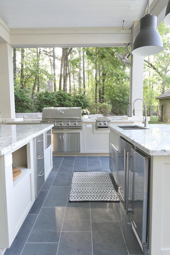 boden aus blauen fliesen und eine graue lampe, eine küche mit einem elektroherd und einem grauen waschbecke, ein garten mit grünen bäumen