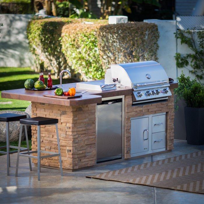 ein garten mitn einer kleinen außenküche mit einem grauen waschbecken und einem elektroherd, eine outdoor küche selber machen