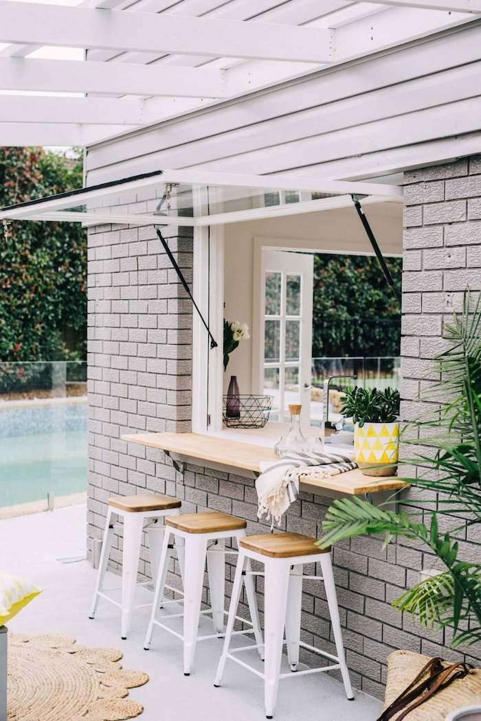 dreim weiße stühle aus holz und ein pool im garten, eine gelbe vase mit grünen pflanzen